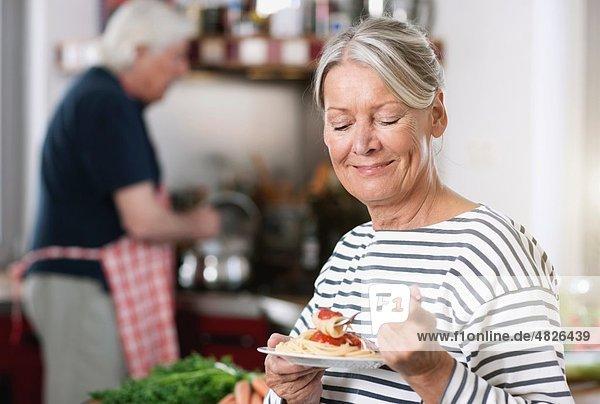 Seniorin beim Nudelessen  Mann beim Kochen im Hintergrund