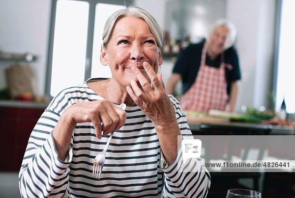 Seniorin schmeckt Nudeln  Mann kocht im Hintergrund