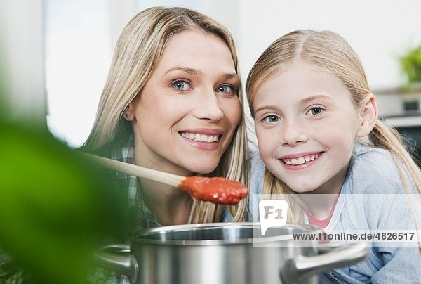 Deutschland    Mutter und Tochter bereiten Sauce zu  lächelnd  Portrait