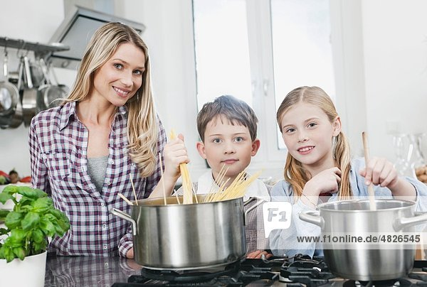 Germany    Mother and children preparing food in kitchen  smiling  portrait