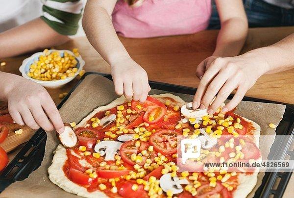 Deutschland    Mutter und Kinder beim Garnieren von Pizza