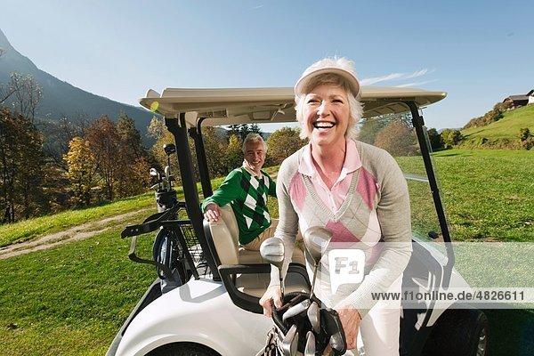 Italien  Kastelruth  reifes Paar im Golfwagen auf dem Golfplatz  lachend