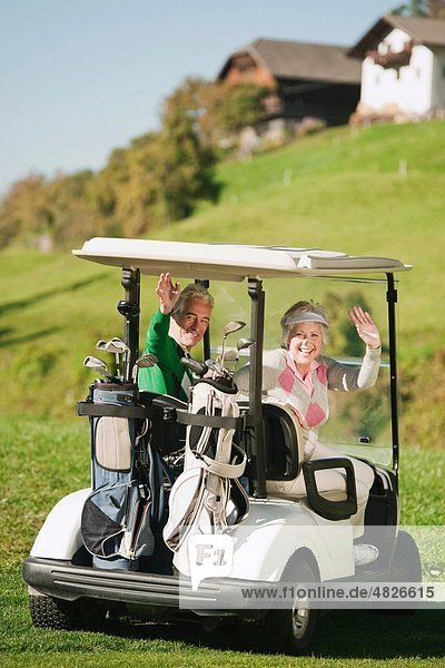 Italien  Kastelruth  Erwachsenes Paar im Golfwagen auf dem Golfplatz  lächelnd  Portrait