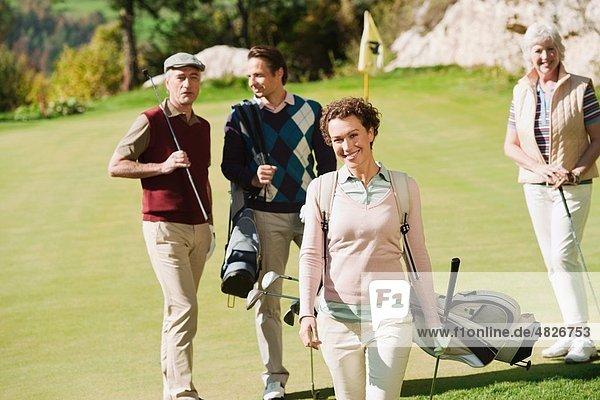 Italien  Kastelruth  Mittlere erwachsene Frau lächelnd mit Golfern im Hintergrund auf dem Golfplatz