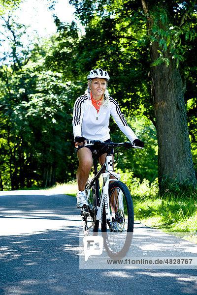 Junge Frau fährt Fahrrad im Park