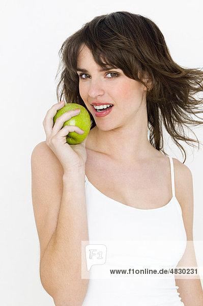 Porträt einer jungen brünetten Frau beim Apfelessen