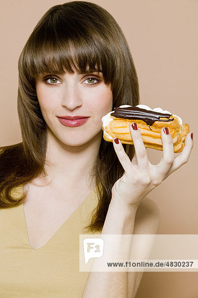 Young woman holding chocolate eclair