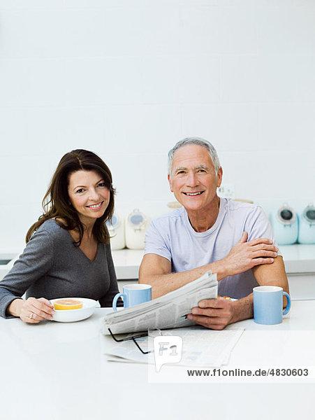 Reife Paare beim Frühstücken  Zeitung lesen