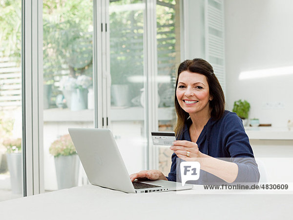 Reife Frau mit Laptop und Kreditkarte