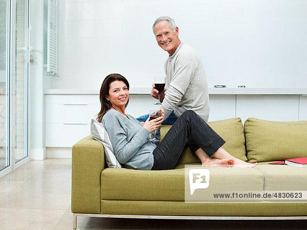 Erwachsenes Paar auf dem Sofa sitzend mit Wein