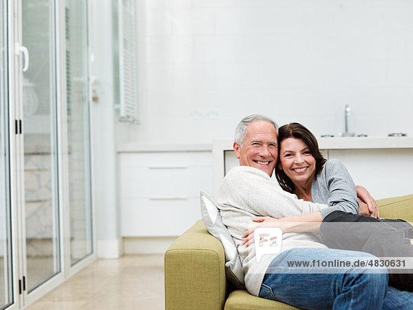 Erwachsenes Paar  das sich auf dem Sofa umarmt