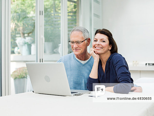 Reife Paare mit Laptop und Kreditkarte
