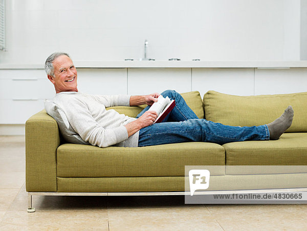 Älterer Mann auf Sofa sitzend Lesebuch