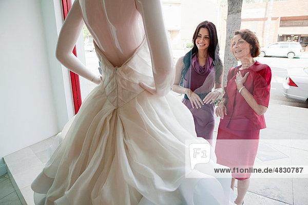 Mutter und Tochter beim Anblick des Hochzeitskleides im Schaufenster
