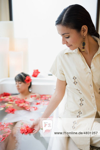 Junge Frau entspannt im Aromatherapiebad mit Blütenblättern