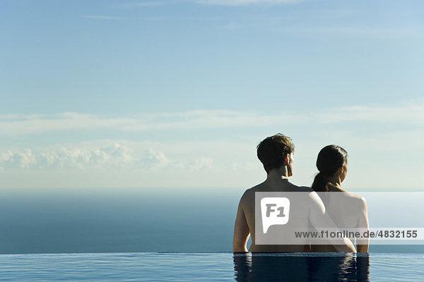 Paar steht am Rand des Unendlichkeitsbeckens und schaut auf die Ansicht