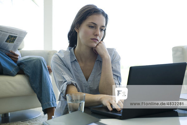 Junge Frau sitzt am Couchtisch und benutzt einen Laptop