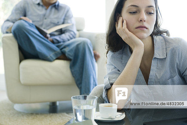 Woman leaning on elbow looking sad  man reading on sofa in background
