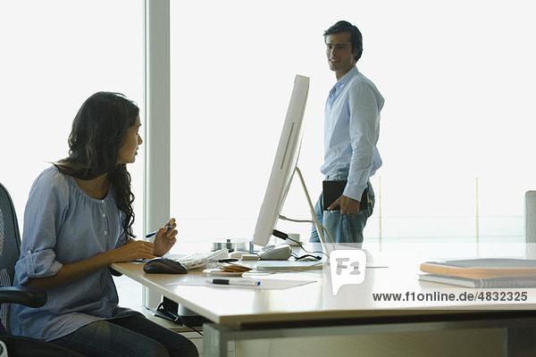 Frau bei der Arbeit am Computer zu Hause  im Gespräch mit dem Ehemann