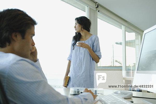 Frau steht mit Tasse Kaffee  schaut aus dem Fenster  Mann arbeitet am Computer im Vordergrund