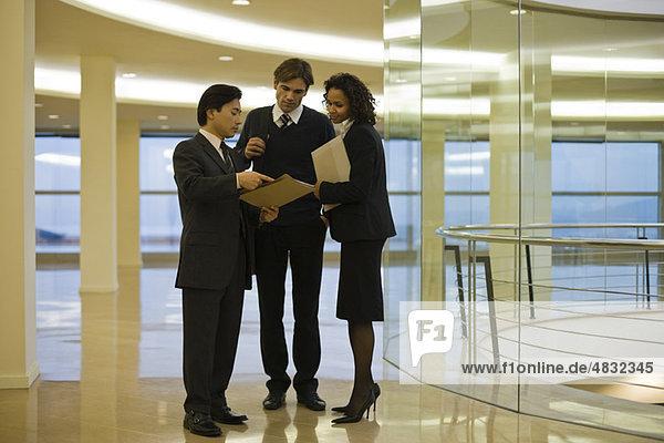 Geschäftsleute stehen zusammen und diskutieren über das Dokument