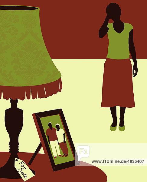 Traurige Frau schaut auf Foto ihrer Eltern