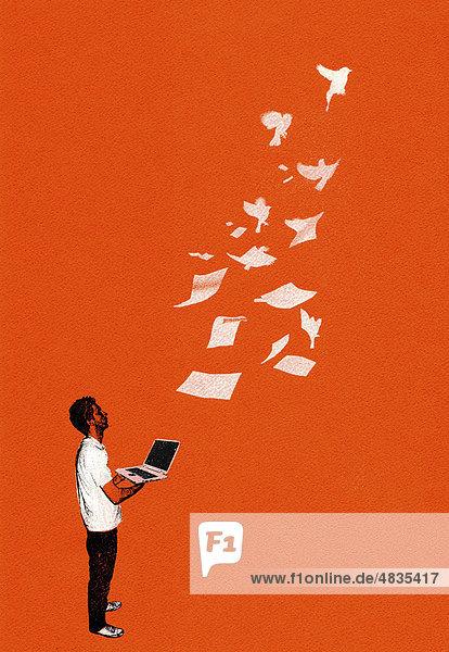 Mann mit Laptop sieht Papiere wegfliegen