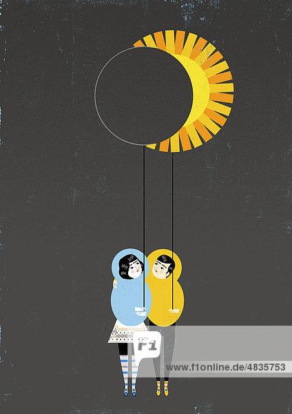Paar hält Luftballons in Form von Sonne und Mond
