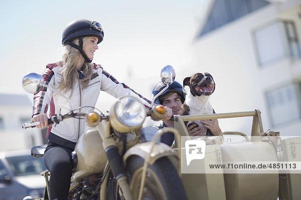 Paar mit Hund beim Motorradfahren