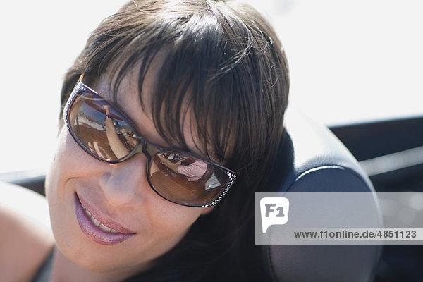 Woman with dark hair and big shades