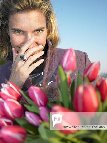 Mann  der einer Frau Blumen anbietet.
