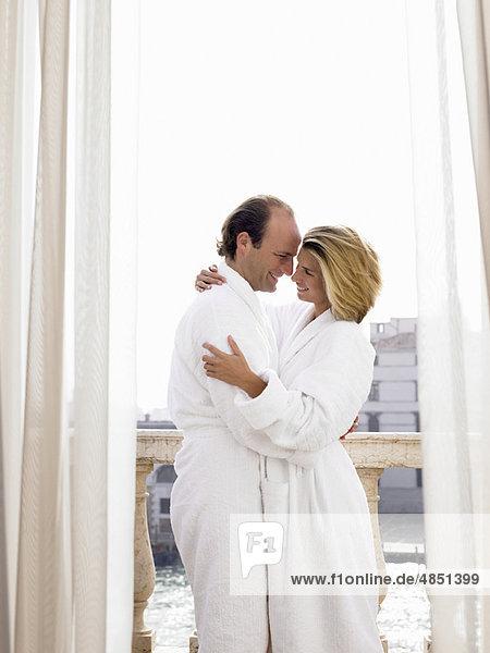 Paar im Bademantel auf dem Balkon