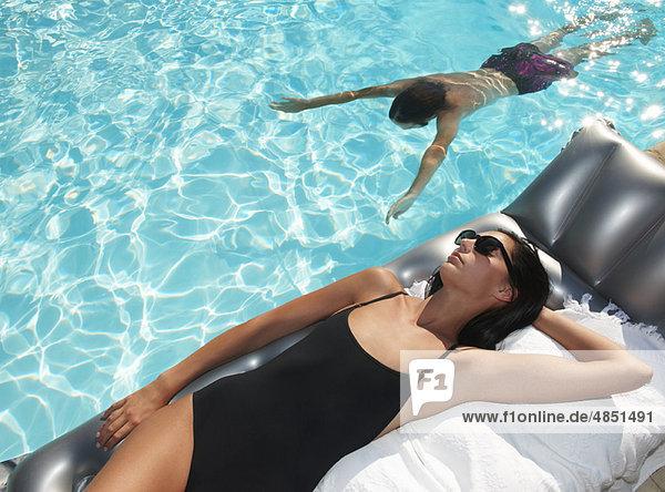 Frau bräunt am Pool  Mann schwimmt