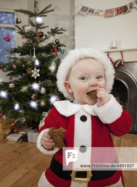 Ein als Weihnachtsmann verkleidetes Baby  das einen Keks isst.