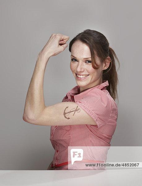 Frauen mit Anchor Tatoo zeigen Muskeln