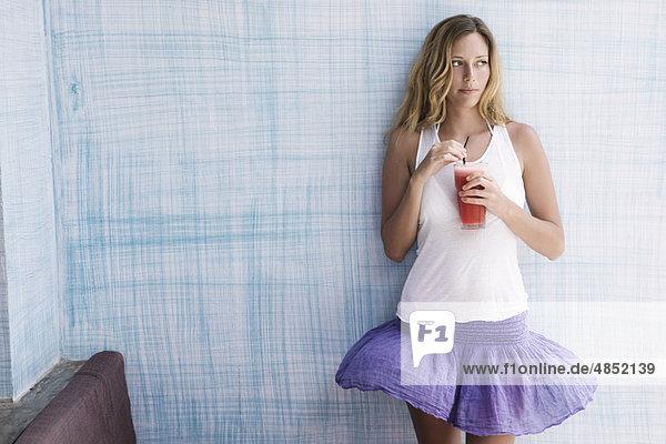 Mädchen steht an blauer Wand mit rotem Smoothie in der Hand