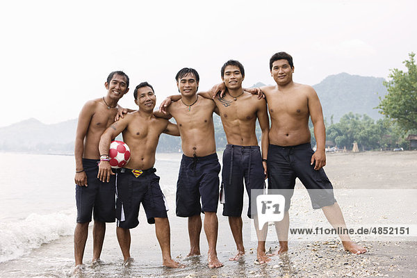 Guys posing for camera on beach