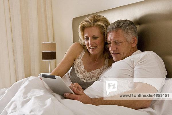 Paar im Bett mit Tablet-Computer