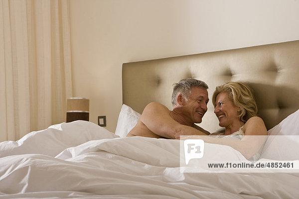 Ein reifes Paar  das sich zärtlich im Bett umarmt.