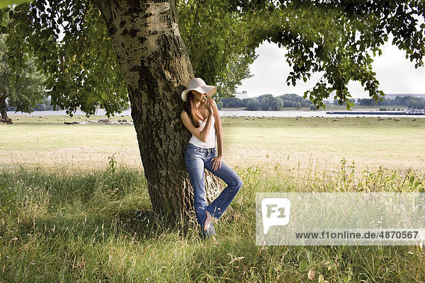 Young woman eating lolly at tree