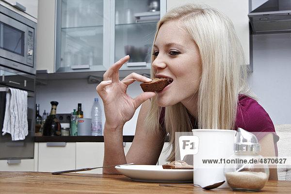 Blonde junge Frau isst Gebäck