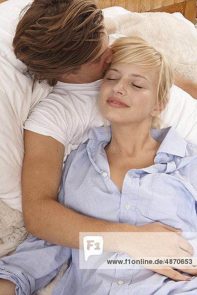 Zärtliches junges Paar liegt im Bett