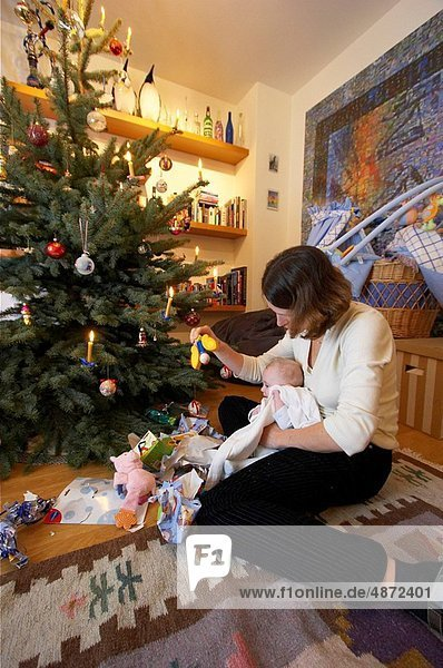 mother with baby opening christmas presents