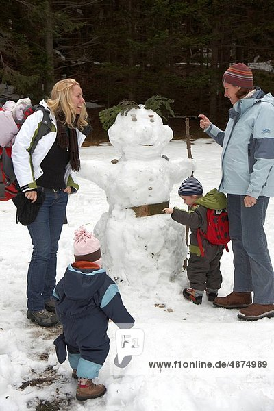 two female friends with children having fun building a snow_man
