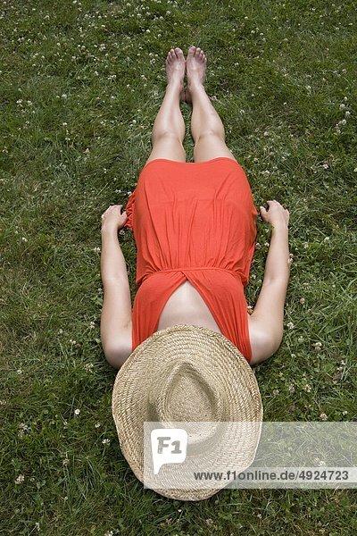 Junge Frau liegt auf einer Wiese mit Strohhut über ihrem Gesicht