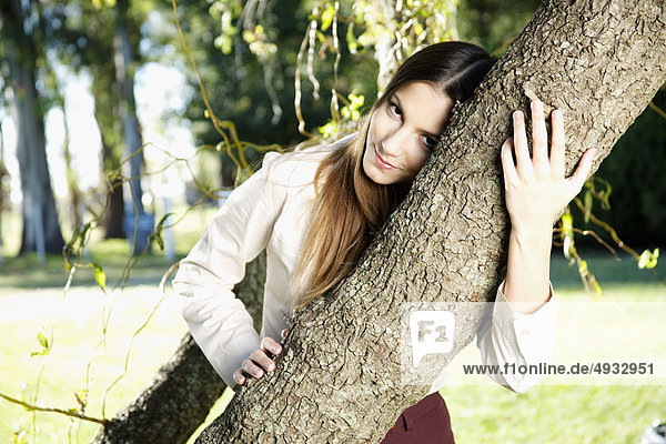 Portrait of a teenage girl hugging a tree in a park
