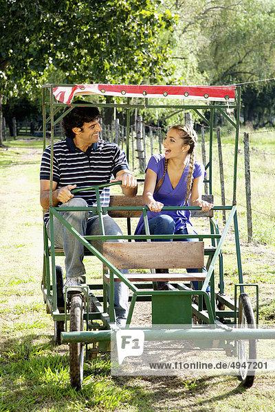 Paar eine Pedale Kart fahren und lächelnd