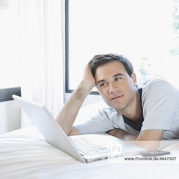 Man lying on the bed in front of a laptop