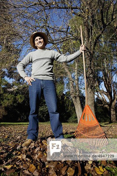 Man raking leaves in a park
