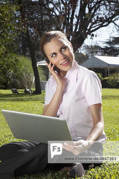 Geschäftsfrau Gespräch auf einem Handy mit einem Laptop in einem park